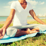 close up of man making yoga exercises outdoors